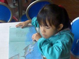 オイスカから寄附された本で一生懸命勉強する1年生の女の子