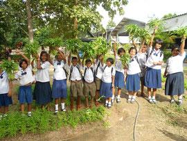 自分で栽培した野菜を手に笑顔の子どもたち。