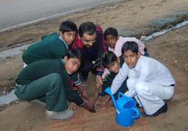 先生と一緒に植林する子どもたち