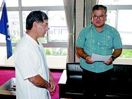 知念辰憲議長に請願書を手渡す上地会長(右)=19日午前、石垣市議会議長室