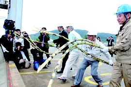 操業の安全を祈願し、コンベアにさとうきびを投げ入れた(右)。石垣島製糖の17/18年期操業が始まった(下)=6日、石垣島製糖