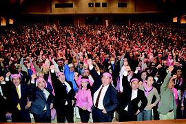 総決起大会で、宮良氏(中央)の必勝を期してガンバロー三唱する支持者=21日夜、市民会館大ホール