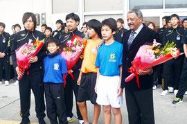 歓迎式で、ブラジル出身のセホーン監督(右端)らに歓迎の花束が渡された=石垣空港