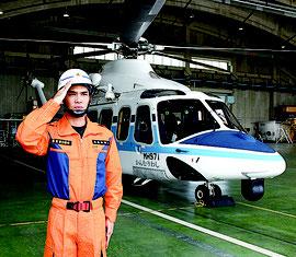 使用ヘリの前で敬礼する外間さん。京都にある海上保安学校を卒業後、那覇や名護、石垣、宮古の巡視船艇で勤務してきた=10日
