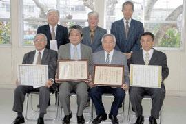 文化財指定書などを手に記念撮影する豊川敏彦さん(前列左から3番目)ら=今年1月10日、市教委