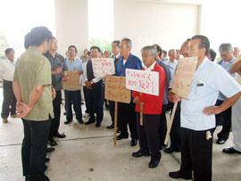 タクシー乗務員が集まり、無料シャトルバスの廃止を訴えた=17日午後、石垣市役所前