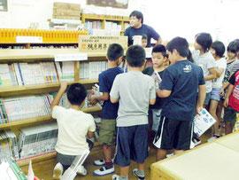 貸し出しが始まった図書コーナーの前で競うように本を手にする児童たち=8日、同校図書室