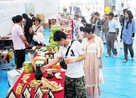八重山の産業まつりで大勢の人たちが足を止めた台湾業者のブース=12日午前、屋内練習場