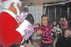 サンタクロースからプレゼントを受け取る子ども=24日午後9時過ぎ、石垣市平得