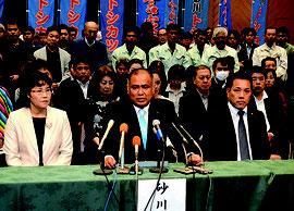 石垣市長選に出馬表明する砂川氏(中央)。左は妻・周子さん、右は仲嶺忠師市議=24日午前、市内ホテル