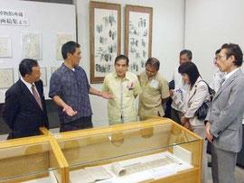写真 高良館長(左から2人目)から展示している古文書の説明をうける関係者ら=22日午前、市立図書館