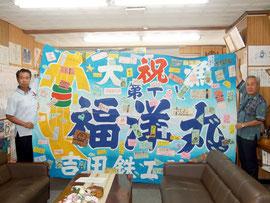 応援メッセージを縫いつけた大漁旗の完成を報告した竹富町=30日午前、町長室