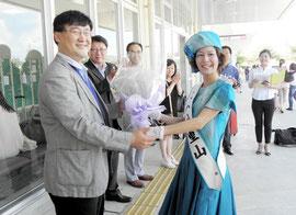 ミス八重山の古謝さんから花束を受けるチェ常務(左側)=石垣空港