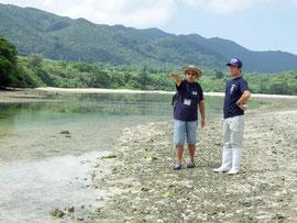 辻所長の案内で、川平湾に浮かぶ小島の周辺を視察した箕底議員(右)=13日午前、川平
