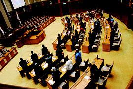 百条員設置に賛成して起立する自民党議員(手前)。与党の反対多数で否決された=29日午後、県議会