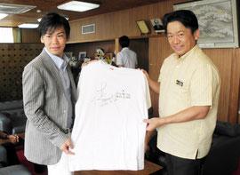 サイン入りTシャツをプレゼントした新城選手(左)=29日午前、市役所