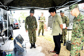 訓練で使用する通信機器について自衛隊員から説明を受ける中山市長=12日午前、バンナ公園