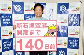 カウントダウン初日となる「開港まで140日」のボードを持つ中山市長。18日、フェイスブックに掲載された(市提供写真)
