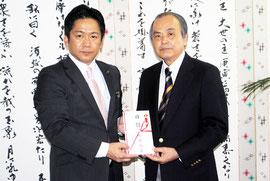 国債1億円の目録を中山市長に手渡す桃原さん(右)=20日午後、市役所
