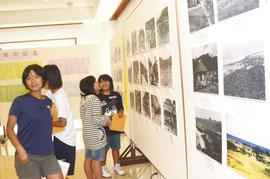 新川小学校の6年生が訪れ、興味深そうに展示を見つめた=八重山平和祈念館、新栄