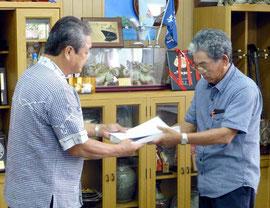 与那国町の外間守吉町長(左)に、住民投票条例の制定を求める署名を手渡す「与那国改革会議」のメンバー=3日午前、沖縄県与那国町役場
