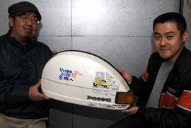 山里さん(写真左)から神奈川メンバーたちによる寄せ書きの書かれたサイドパネルを受け取る東京の関根さん