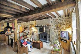 Gîte de Rameix, séjour - salon : pierres et boiseries, cheminée granit avec poêle, TV, Chaine HIFI, éclairage d'ambiance, atmosphère chaleureuse.