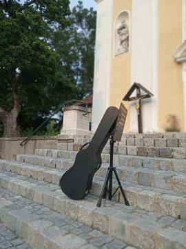 funda de guitarra con atril, árbol e iglesia de Fischamend