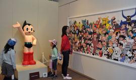 鉄腕アトムの人形や手塚作品オールスターの集合絵などが並ぶ会場