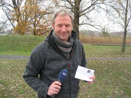 """Jörg Schimmelpfennig mit einer CVJM-Briefmarke zum 60-jährigen Jubiläum des CVJM Wolfsburg zum Arbeitsbereich  """"Sport im Strafvollzug"""