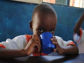Junior trinkt Haferbrei. Das Mittagessen bringt den MiRO-Kindern stets eine der Hausmütter.