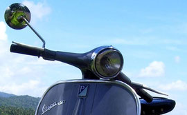 Vespa in front of white and blue sky