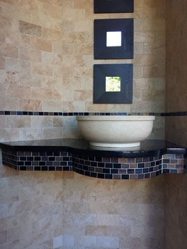 A tumbled travertine feature wall with a glass mosaic, a Black Galaxy countertop, and a carved vessel sink in our Kent showroom, a short drive from Federal Way, Renton, and Auburn