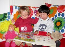 Die Kinder schauen sich ein Bilderbuch zusammen an