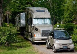 Ein Monster Volvo mit riesigem RV und zusätzlichem Smart auf Plattform