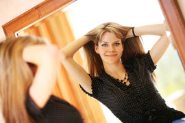 Young woman looking in mirror at new hairstyle