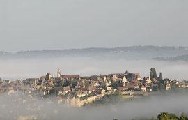 Domme dans la brume matinale