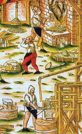 """Die Verarbeitung von Eisenerz in einem Hammerwerk. Darstellung aus dem Werk """"De re metallica libri XII. aus dem Jahre 1556."""