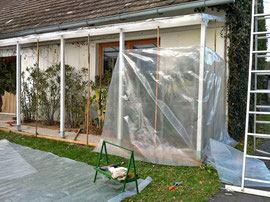 A plastic-sheeting shelter is being built