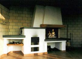 Diese Grillstelle auf einem gedeckten Sitzplatz wurde kombiniert mit einem Backofen. Als Arbeitsfläche dient ein Sandstein. Integriert wurde auch ein Holzfach, sowie eine Ablage für Grill -und Ofenbesteck.