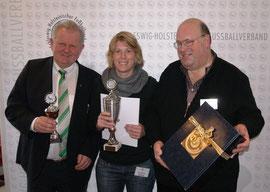 Ehrung durch den Präsidenten des SHFV Hans-Ludwig Meyer (li.) und den stellvertretenden Vorsitzenden des Schiedsrichterausschusses Siegfried Scheler (re.)