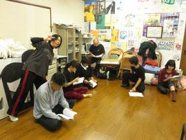 神妙にヤナギサワさんの演出ノートを聞く劇団員+カメラを向けられるとポーズをとらずにいられない劇団員約1名