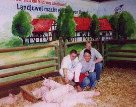 """Die """"Jugendredaktion"""" der Online-Zeitung. 3 Azubis am Landjuwel-Stand mit Ferkeln. IGW Januar 2003. Foto: Helga Karl"""