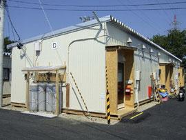 結露が発生せず、好評だったウエキハウス(株)の木質住宅(写真は中越沖地震建設された仮設住宅)。外観は木質パネルに角波鉄板を張っている。現在は、木質パネルと鉄板を一体化したパネルも開発し、施工期間はさらに短くなった