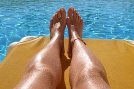 2 Beine auf einer sonnigen Liege. Im Hintergrund das Wasser des Pools