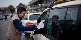"""Bitte geht nicht zu dieser Demo!"""", steht auf seinen Zetteln: Taxifahrer Jörn Napp verteilt Flugblätter an seine Kollegen.       Bild: Miguel Ferraz"""
