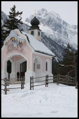 """Spektakuläres Fotomotiv: Die Kapelle """"Maria Königin"""" am Lautersee vor dem Wetterstein-Massiv."""
