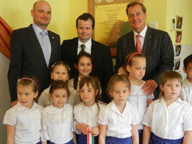 Balról: Mag. Molnár András, városi képviselő, Csicsely Tamás, a Forum Hungaricum képviseletében és Mag. Rudi Roth,  Magyarország tiszteletbeli konzulja devecseri óvodásokkal