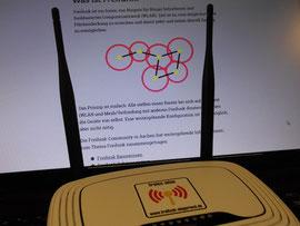 """Das anliegende Foto zeigt einen """"Freifunk-Router"""" vor einem Ausschnitt aus der Homepage von Freifunk Siegerland. Das Foto ist frei verwendbar mit der Quellenangabe: dbf"""