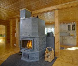Wohnblockhaus - Blockhaus - Wohnzimmer mit Specksteinofen als Wärmequelle - Heizapparat - Heizgerät - Heizkörper - Heizung - Heizvorrichtung - Feuerstelle - Kaminofen - Holzheizung